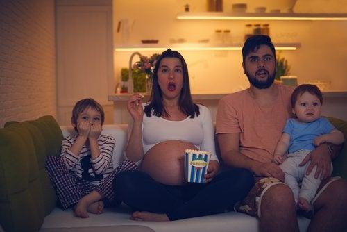 Perhe katsoo elokuvaa sohvalla